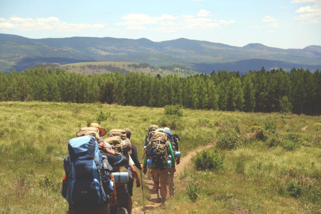 Abbildung zeigt Wander Gruppe mit Rucksack Wander Tour in den Bergen auf Hüttentour mit Hüttenschlafsack und Isomatte Sportsocken Wandersocken von Wanderer Wandern in Bergen